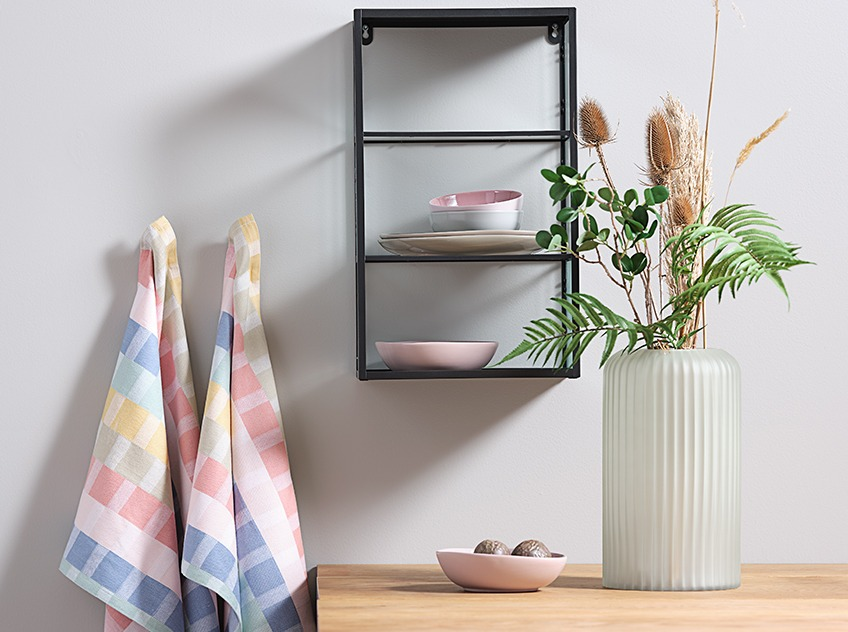 Kitchen wall with hanging shelf, tea towels and vase with artificial flowers on the counter