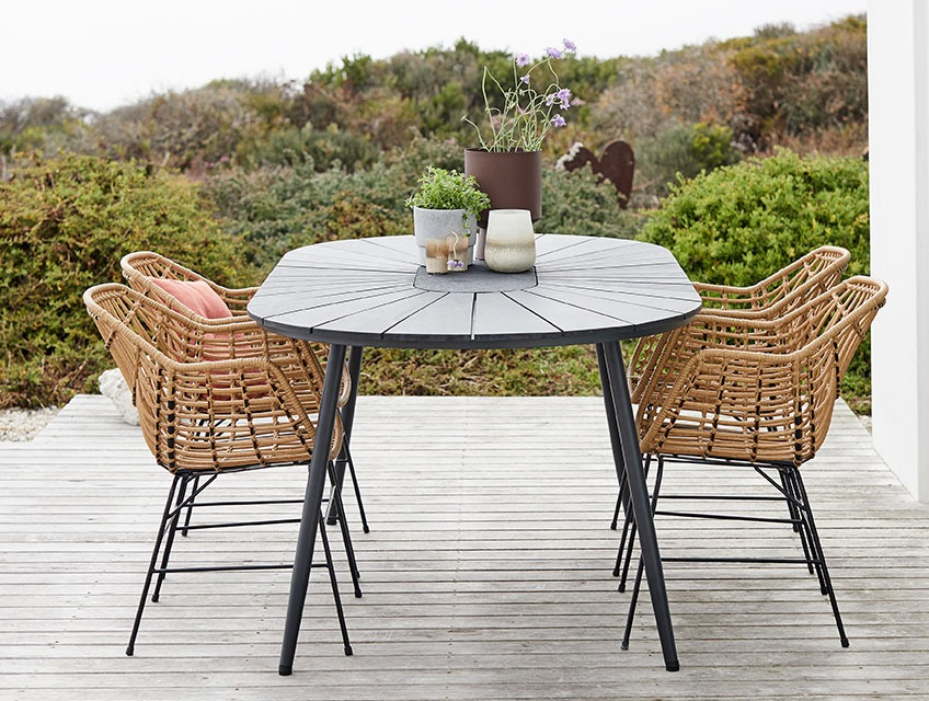Garden dinging set with table in artwood and chairs in rattan on a patio