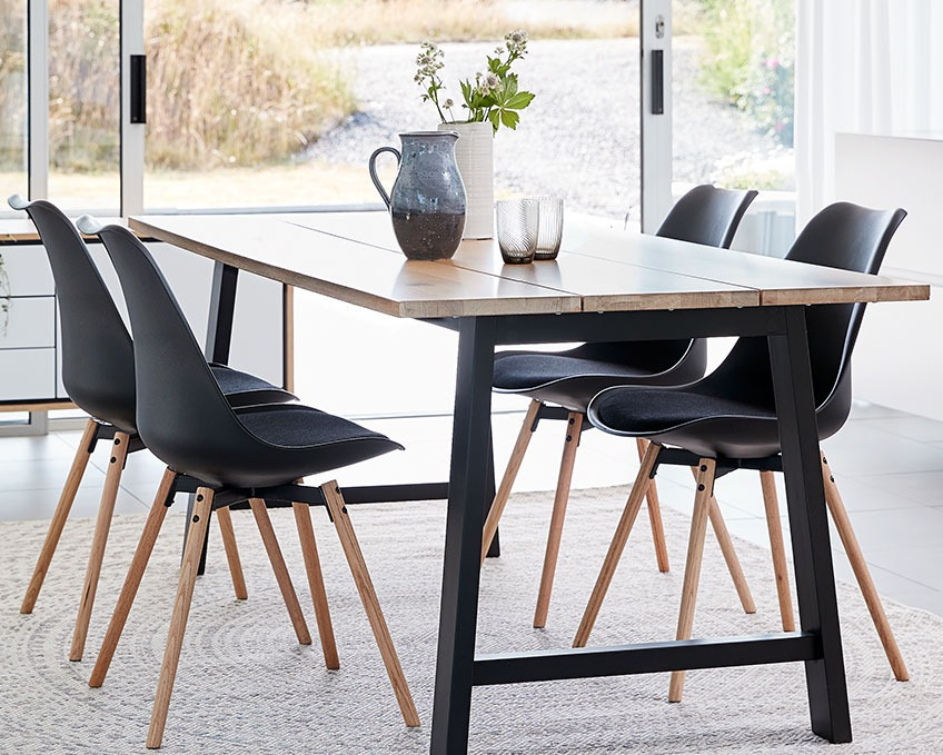Four black dining chairs at a dining table
