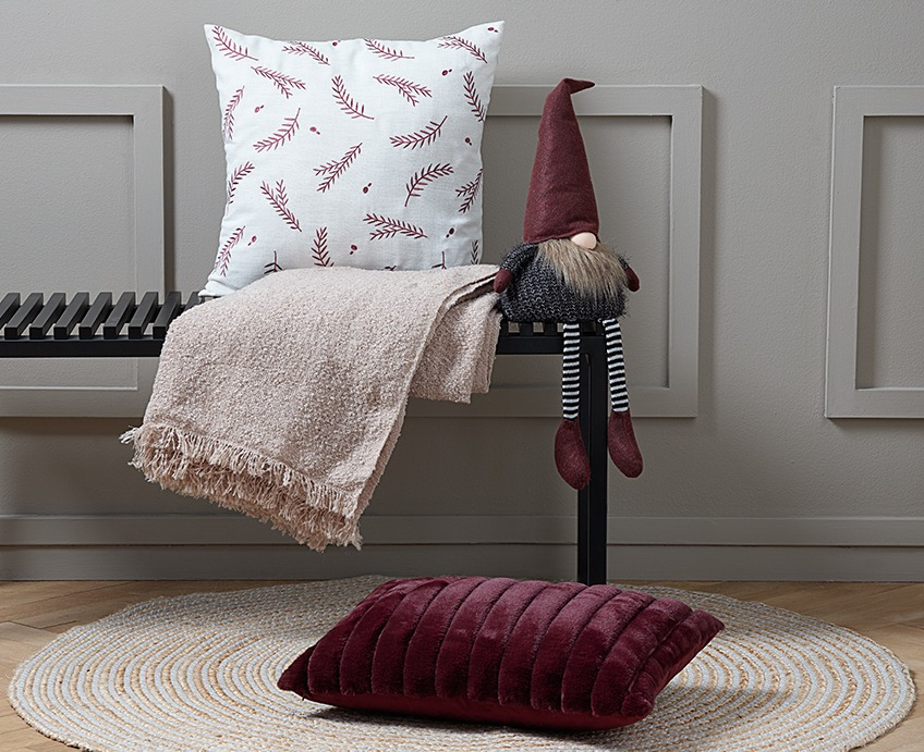 Bench with a cushion, a throw and an elf. On the floor in front of the bench, a red cushion on a round rug.